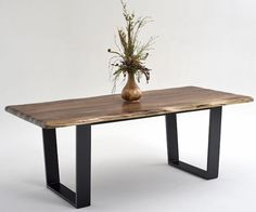 Contemporary rustic dining table made from solid black walnut with an organic, live edge and solid forged metal