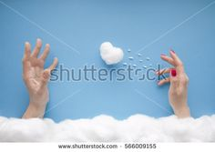 A men's hand catching a heart thrown by a woman's hand with red nails, in a heavenly scenery with clouds made of cotton-wool, on a blue sky paper background.