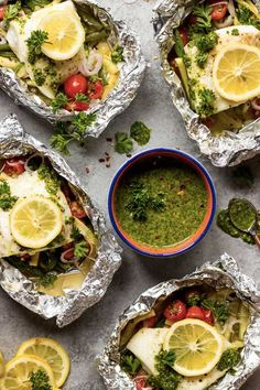 Baked fish and vegetable in foil with chimichurri sauce. 15 Foil-Packet Dinner Recipes that Make Cleanup a Breeze #purewow #dinner #grilling #easy #food #recipe #cooking #foilpacketrecipes #foilpackets #campingrecipes #bakedfish #seafoodrecipes #seafood