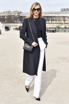 beautifully put together, white trousers, dark sweater, long coat and beautiful handbag