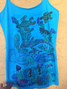 Ladies size large blue cami tank top features an ocean life scene of dolphins, sea turtles, sea horses and sea life, the peace and tranquility of ocean life.. We design custom made clothing by hand using non toxic fabric markers, if you want your pets, nature or a specific design or scene drawn on a T-shirt, Tank Top or Sweatshirt please send us a message telling us what size and color of the clothing you need as well as a photo of the design you want drawn on your clothes. Custom designs…
