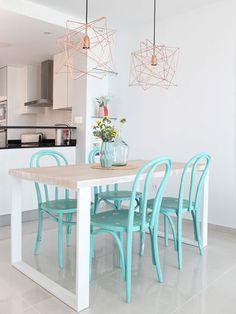 Comedor con mesa de madera y patas blancas y sillas azules