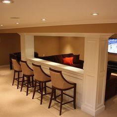 maybe i could faux trim our pillar to get this look?  bar and stools behind couch…in between pillars...