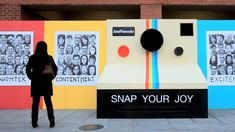 Snap Your Joy is a campaign to encourage people to show their happiness through a big polaroid camera placed on the side of the road. There is a camera to record their act in front of the 'camera'. Later on the pictures are printed on a big board and stick on the wall.