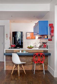 A bancada revestida em madeira de demolição ganha um espaço para refeições rápidas. O visual é despojado, com cadeiras diferentes adquiridas no site SD Online.