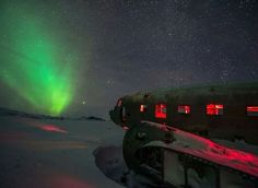 冰岛 Iceland,遗弃的飞机残体被 极光 Aurora 照亮。摄影师:Suranga Weeratunga
