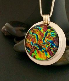 Beautiful dichroic glass pendant in vibrant colors of rust, gold, blue and green in a silver plated bezel setting.