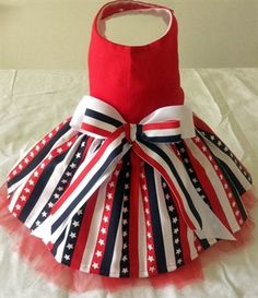 ThePet-Boutique's Exclusive Design! Our striking stars and stripes dress has a red bodice and stars and stripes skirt with red tulle underlay. Our dress is embellished with coordinating bows.  Bodice is lined and the dress is 100% cotton. Perfect for small and big dogs!