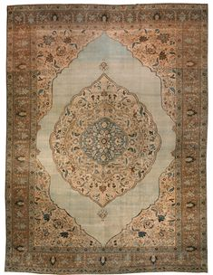 An early 20th century Persian Tabriz antique rug, the open pale field surround concentric cusped medallions with floral motifs in shades of blue, sand beige and brown, with enlarged sand-colored spandrels with palmettes within a tan palmette and scrolling vinery border. Watch full size video of A Persian Tabriz carpet, Circa 1900, ID BB2521 - Video