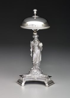 Dinner bell  MAKER William Bogert & Co. (American, 1866 - 1881) DATE c. 1860–1870 DEPARTMENT Decorative Arts And Design DIMENSIONS Overall: 12 1/2 x 6 1/2 x 5 3/4 in. (31.75 x 16.51 x 14.6 cm) MEDIUM Silver LOCATION