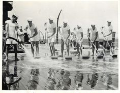 """1941- Seven Patten brothers all serving in the U.S. Navy shown """"swabbing"""" deck aboard the U.S.S. NEVADA in Honolulu."""