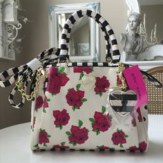 """Betsey Fushia Rose Satchel with Heart swagHPx2 Adorable floral handbag with 2 snap outer pockets on both sides. Inside zip pocket & 2 open pockets on opposite side. 52"""" detachable Crossbody strap. Polka dot sides & heart mirror & key charm. Chosen by Jennifer @jcarr1212 5/12 Best in Bags Betsey Johnson Bags"""