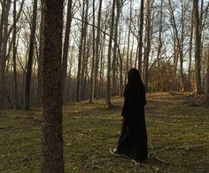 Niqabi walking through the woods