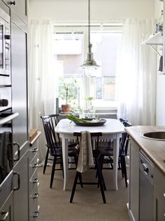 Kitchen cabinets offer plenty of space for storage.  A kitchen, including OTTAVA aluminum suspended luminaire