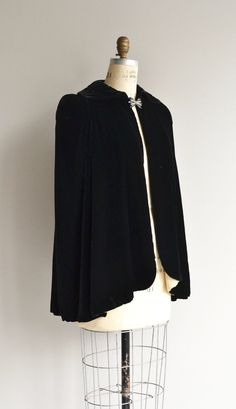 Vintage 1930s black silk velvet cape with lovely black glass and rhinestone bow clasp and eggshell silk lining.  --- M E A S U R E M E N T S ---  fits