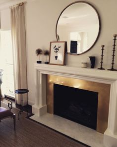 {We designed a custom, antiqued brass surround for our client's fireplace.}