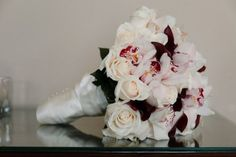 """""""A contemporary bouquet of vendela roses, mini purple calla lilies, cymbidium orchids and accents of phalaenopsis orchid blooms edged with an ivory wrap.""""  - For a girl who hates flowers, I loved my bouquet!"""