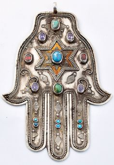 """A hamsa is an amulet shaped like a hand, with three extended fingers in the middle and a curved thumb or pinky finger on either side. It is thought to protect against the """"evil eye"""" and is a popular motif in both Jewish and Middle Eastern jewelry. Hippie Style, Turquesa E Coral, Hand Der Fatima, Hippy Chic, Estilo Hippie, Jewish Art, Tribal Jewelry, Hamsa Jewelry, Jewellery"""