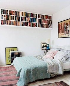 Take storage to the ceiling by securing a few shelves or storage cubbies high above your bed to create a statement piece no one can ignore.