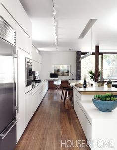 modernist kitchen incorporates a work area and a 22′ island. | Photographer: Rob Fiocca Designer: Larry Mintoff
