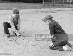 Full-length image of two young boys kneeling on the dirt and playing a game of marbles. One boy flicks a marble into a circle drawn in the dirt.