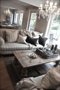 Living Room decor - rustic farmhouse style. Striped sofas, wood coffee table, crystal chandelier, cozy and chic!