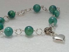 Check out this item in my Etsy shop https://www.etsy.com/listing/216529144/green-beads-and-heart-charm-bracelet