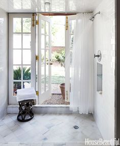 The master bath's nearly alfresco shower has Alabama white marble tile floors and French doors that open onto a pea gravel-bordered lawn. The Costello bronze side table is from Arteriors Home.   - HouseBeautiful.com