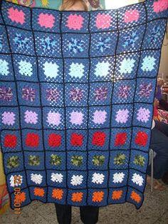 Manta feita com squares de croche multicolorida.
