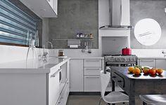 A cozinha foi revestida de tecnocimento e tem móveis brancos, que ajudam a clarear o ambiente. Projeto da arquiteta Claudia Haguiara