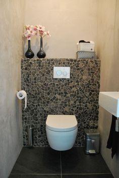 Dans les toilettes, le petit mur en mosaïque de vert et les fleurs pastel font…