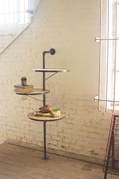 The Three Tier Round Iron & Wood Swivel Shelving Unit features an elegant design with sturdy wooden shelves. This three shelf unit can be just as useful in any room and instantly update a space.Color: