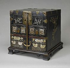 .Cosmetic boxes such as this would have belonged to aristocratic women at the Korean court, and were used to store combs, hairpins, jewellery and cosmetics. This box, which dates from the nineteenth century, has been decorated using inlaid mother-of-pearl. The front face is adorned with scrolling foliage, Korean seal characters, and a pair of ducks in a pond surrounded by lotus plants.