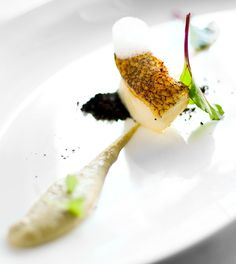 Merluza negra fish cooked sous vide with artichoke hearts cream, sea air and black olive powder.