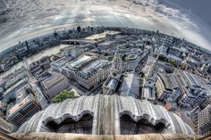 A landscape photograph of the London cityscape from the dome of St Pauls Cathedral taken with a fisheye lens. The scene shows the Cathedral, River Thames, London Eye, Millennium Bridge and the Tate Modern art gallery.