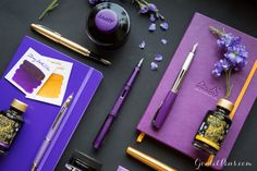 Powerful writing comes from purple and gold fountain pens, paper, and ink. What a gorgeous collection!