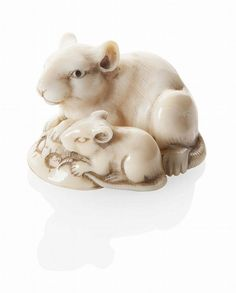 JAPANESE CARVED IVORY NETSUKE 18TH/19TH CENTURY depicting a rat and its young sitting over a curved aubergine base, the mature rat's tail coils around beneath her body, her eyes inlaid in black horn 4cm long