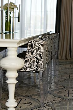 patterned tile floor, lacquered table, lucite chairs