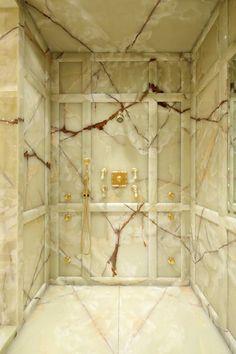 Onyx shower walls, floor and ceiling. Light beiges with striking dark brown veins.