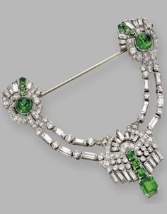 Emerald and diamond jabot, circa 1930. Designed as a swag of baguette, round and single-cut diamonds, supporting a fringe set with emerald-cut emeralds, supported by cabochon emeralds framed by baguette, round and single-cut diamonds at the terminals of the pin, mounted in platinum. #ArtDeco #jabot #brooch ~ETS