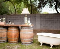 old clawfoot bathtub for holding drinks and barrels holding up the bar!