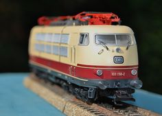 Märklin H0 - The BR 103 from the Deutsche Bahn. I always loved those rich colours.  German Federal Railroad (DB) class 103.1 electric locomotive in crimson/beige. With two rows of side vents, without end skirting, with buffer cladding, and single-arm pantographs. Used in IC service. The locomotive looks as it did at the start of the Eighties.