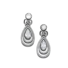 Pair of diamond ear clips, Hemmerle. Each collet-set with a circular-cut diamond, suspending a pear-shaped diamond, accented with a small bow motif, highlighted with brilliant-cut stones.