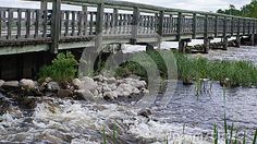Foot bridge over a small damn at the edge of a lake regulating the flow of water into a river