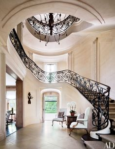 A chandelier from Mecox hangs in the entrance hall, where a wrought-iron balustrade lines the serpentine staircase; the faux-limestone walls are by decorative painter Jerzy Kubina, and the circa-1890 Régence-style sconce is from David Duncan Antiques.