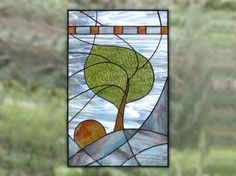 MADE TO ORDER 13 x 20 stained glass panel depicting a tree on a bare mountain edge swaying in the wind, its leaves rustling. Shreds of milky fog are swirling around. The sun is just peeking out and does not yet bring in enough light to warm up the landscape. The colors are bright