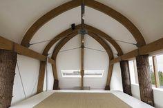 Een huis opgebouwd uit boomstammen .De houten vloer in de loft tussen de boomstammen halveert de kniklengte van de bomen.