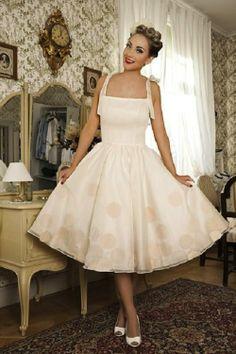 """""""Dolly Couture hace las delicias de las novias que quieren llevar un vestido retro años 50 o 60. El vestido de la foto se ha realizado en raso y organza, adornado con unos lunares en organza rosa sobre el tul y el raso. Los tirantes se atan en forma de lazo y el cuerpo va sujeto con ballenas para mayor comodidad de la novia."""""""