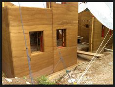 Beveled rammed earth wall sections with windows...