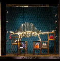 @Louis Vuitton Official store windows: A gilded dinosaur walks amongst a collection of Alma bags.